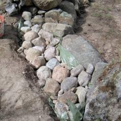 Tausta täytetty kivillä. Kevytpeite suojaa maata veden aaltojen varalta.